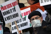 Activists hold signs during a rally at New York's City Hall to call for immediate action on paid sick days legislation in light of the continued spread of the flu in  Jan 2013.