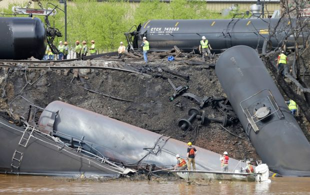 Survey crews in boats look over tanker cars as workers remove damaged tanker cars along the tracks where several CSX tanker cars carrying crude oil derailed and caught fire along the James River near downtown Lynchburg, Va., Thursday, May 1, 2014. Virginia environmental officials have proposed a $361,000 civil fine against CSX Transportation Inc. as punishment for a 2014 derailment that saw nearly 30,000 gallons of Bakken crude oil dumped in and around the James River.