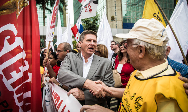 Scott Courtney, a leader of the Fight for 15 campaign, with protesters in Brazil. Credit Fernando Cavalcanti