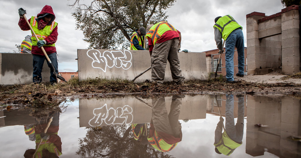 Panhandlers dug up weeds along a side street in Albuquerque as part of a new program in the city. Credit Mark Holm for The New York Times
