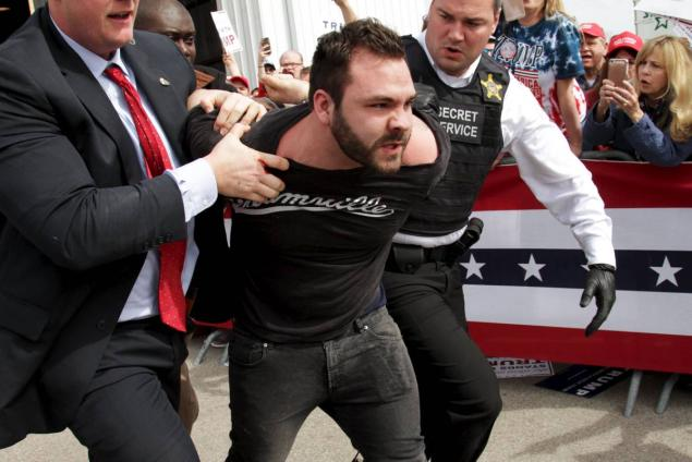 WILLIAM PHILPOTT/REUTERS Authorities detain a protester on Saturday at Trump's rally in Dayton, Ohio.