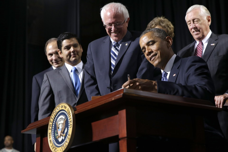 Senator Bernie Sanders watches as President Obama signs the Veterans' Access to Care through Choice, Accountability, and Transparency Act of 2014. Jacquelyn Martin/AP