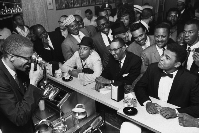 Malcolm X joking around with Ali at a diner in 1964