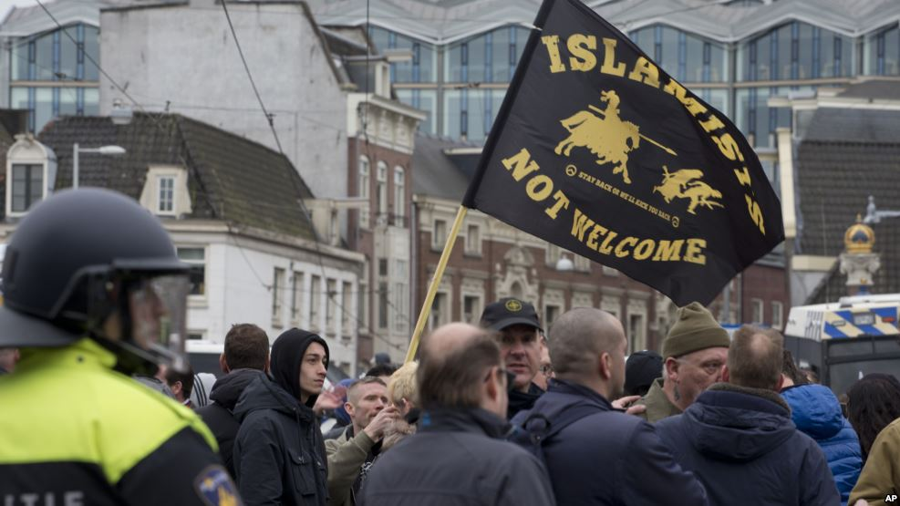 "Riots police separate pro and anti immigration demonstrators as a man waves a flag reading ""Islamists Not Welcome"" during a Pegida demonstration in Amsterdam, Netherlands, Feb. 6, 2016."