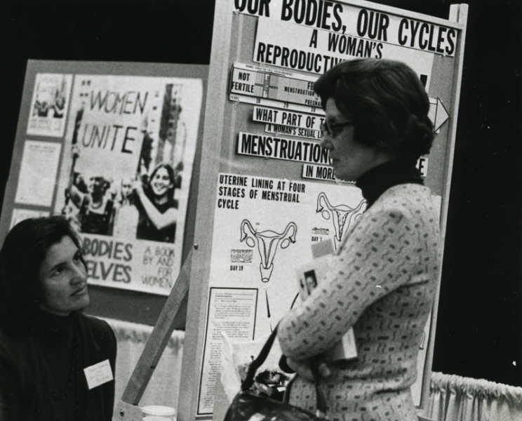Norma Swenson and Betsy Cole at an exhibit booth for Our Bodies, Ourselves
